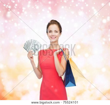 shopping, sale, gifts, money and holidays concept - smiling woman in red dress with shopping bags and money over pink snowy background