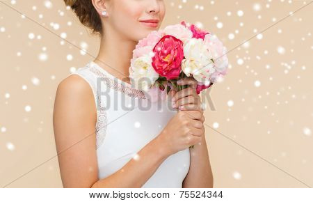 happiness, wedding, holidays and celebration concept - close up of smiling bride or bridesmaid in white dress with bouquet of flowers over beige background and snow