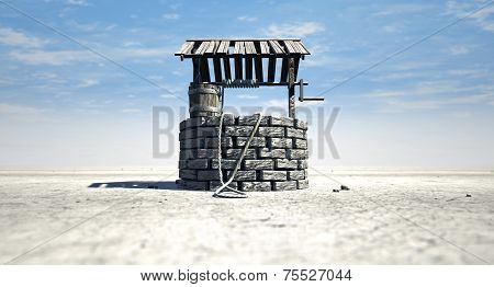 Wishing Well With Wooden Bucket On A Barren Landscape