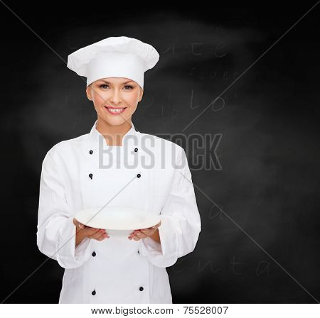 people, cooking and food concept - smiling female chef, cook or baker with empty plate over blackboard background