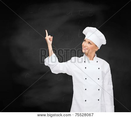 cooking, advertisement and people concept - smiling female chef, cook or baker pointing finger up to something over blackboard background