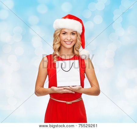luxury, advertisement, holydays and sale concept - smiling woman in santa helper hat with white blank shopping bag over blue lights background