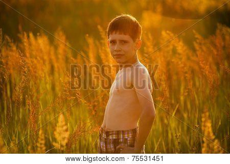 Boy Standing Among Tall Grass