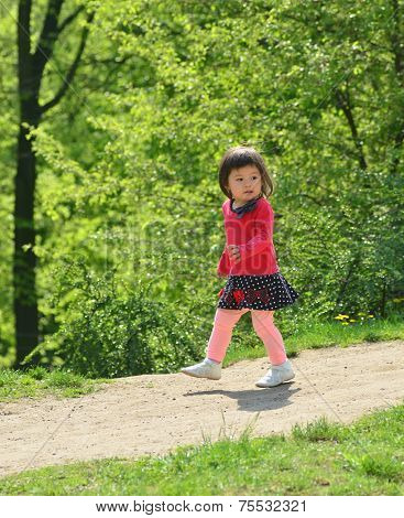 2 years old girl walking down the hill. Asian ethnicity. Summer green background
