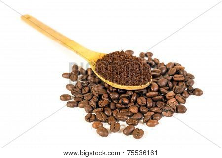 Ground Coffee On Wooden Spoon. Lots Of Coffee Beans Scattered On Background