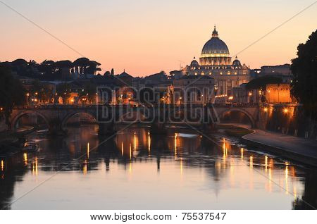 Monumental St. Peters Basilica over Tiber at sunset in Rome, Italy
