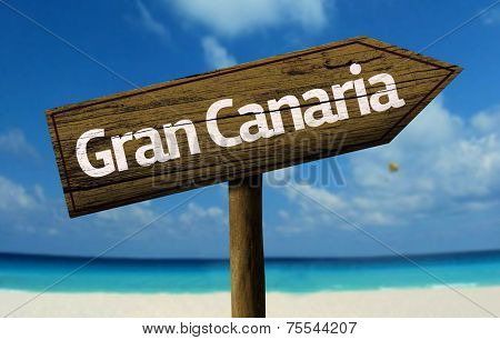Gran Canaria wooden sign with a beach on background