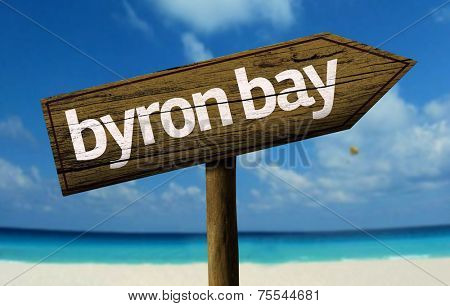 Byron Bay, Australia wooden sign with a beach on background