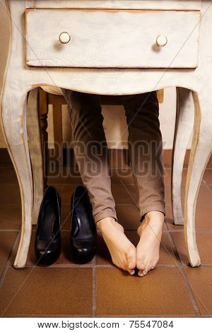 Bare Female Feet Under The Vintage Table.