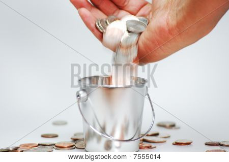 Hand Pouring Coins into a Bucket