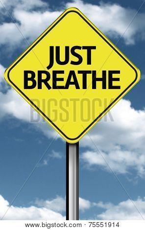 Just Breathe creative sign on a beautiful sky