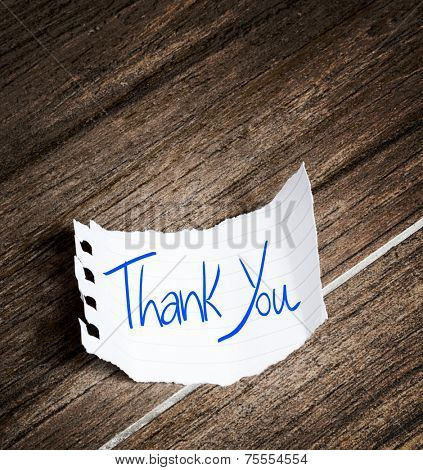 Thank You written on the paper on a wood background