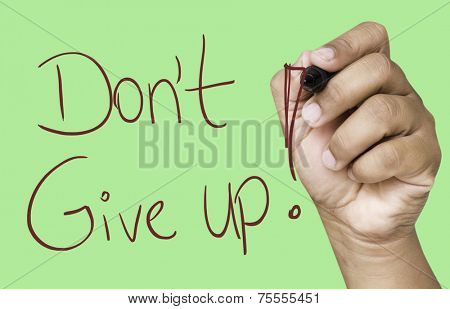 Don't Give Up hand writing with red marker on transparent wipe board