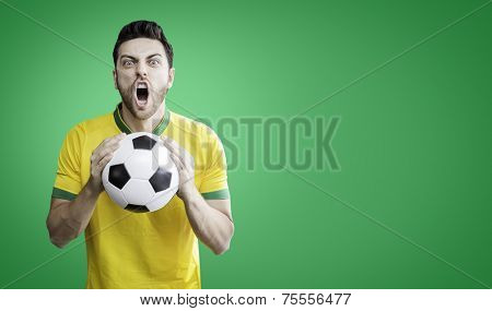 Brazilian man holding a soccer ball celebrates on the green background