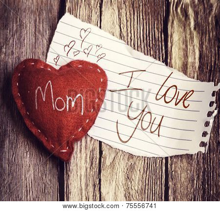 I Love You Mom written on a peace of paper and a heart on a wooden background, with retro filter effect