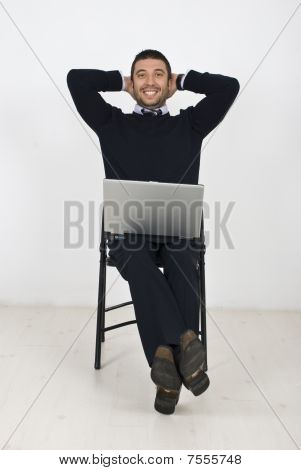 Happy Businessman With Laptop On Chair