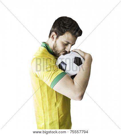 Brazilian man celebrates kissing a soccer ball on a white background