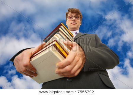 Man With Big Stack Of Books Against Sky