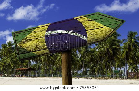 Brazil flag wooden sign with a beach on background - Oceania