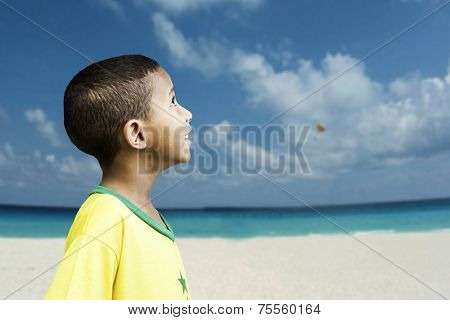 Brazilian little boy looks to the sky on the beach