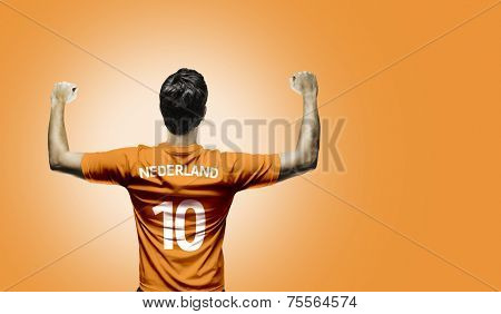 Dutchman soccer player celebrates on orange background
