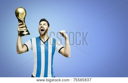 Argentinian soccer player celebrates the championship holding a trophy on blue background