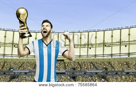 Argentinian soccer player celebrates the championship holding a trophy in the stadium