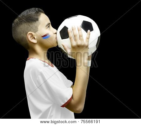 American little boy kissing a soccer ball on black background