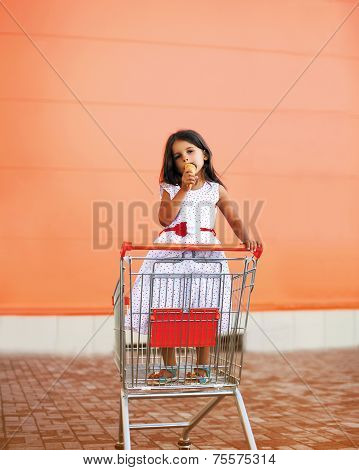 Little Girl In Shopping Cart With Icecream