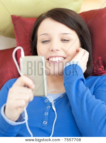 Pretty Young Woman Listening Music Lying On A Sofa