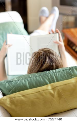 Blond Woman Reading A Book Lying On A Sofa
