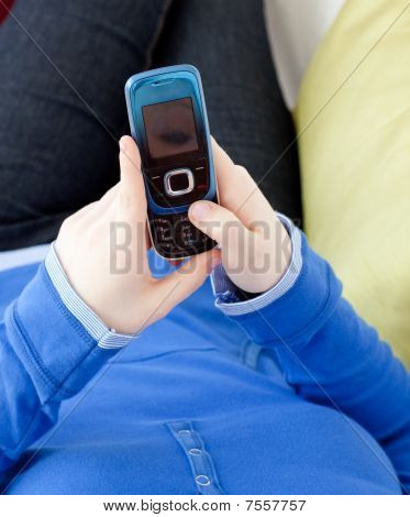 Close-up Of A Woman Sending A Text Lying On A Sofa