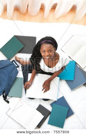 Cheerful Teen Girl Studying Sitting On Her Bed