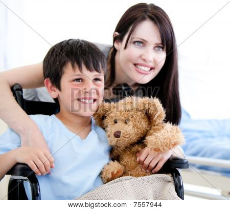 Smiling Little Boy In A Wheelchair With His Mother