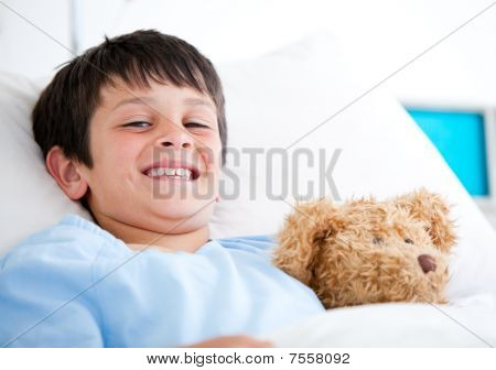 Smiling Little Boy Lying In A Hospital Bed