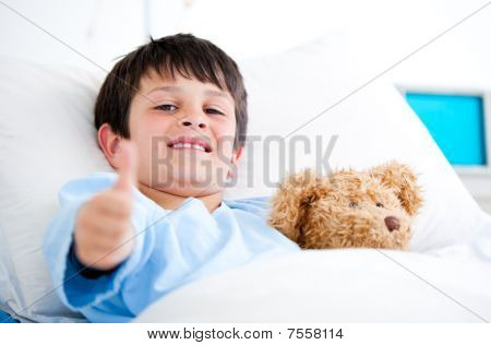 Little Boy Hugging A Teddy Bear Lying In A Hospital Bed