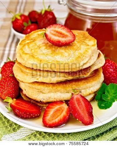 Flapjacks with strawberries and honey on tablecloth