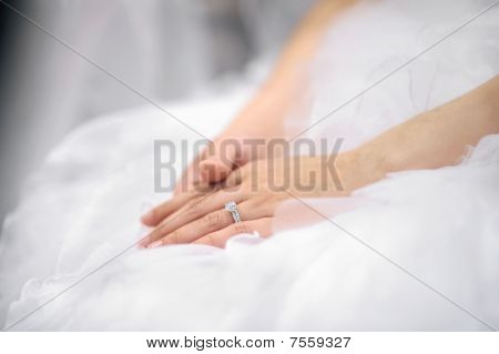 Bride's Hands Laying On Wedding Dress