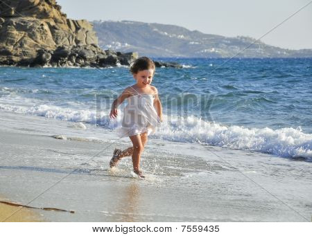 Child In A White Dress Running Through The Waves