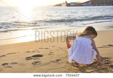 The Little Girl Playing At Sunset Near The Sea