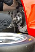 pic of work crew  - Pit crew mechanic working on the brake pads and brake disc of a red race car - JPG