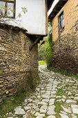 stock photo of old stone fence  - Old building made of stone roof tiles in Bulgaria - JPG