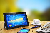 stock photo of stock market data  - Modern black glossy tablet PC with colorful touchscreen interface of stock exchange market application - JPG