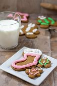 picture of christmas cookie  - Several gingerbread Christmas cookies on a white plate with cookie cutters a rolling pin and several cookies in the background.