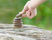 stock photo of zen  - Zen concept Hand put stone building a pile of zen stones - JPG