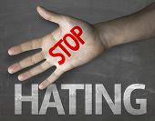stock photo of stop hate  - Educational and Creative composition with the message Stop Hating on the blackboard - JPG