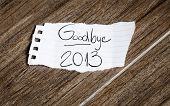 stock photo of goodbye  - Goodbye 2013 written on the paper on a wood background - JPG