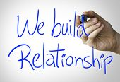 picture of courtesy  - We build relationship hand writing on blue marker on transparent wipe board - JPG