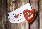 "image of miss you  - ""Mae, Te Amo"" (In portuguese - Mother, I Love You) written on a peace of paper and a heart on a wooden background - JPG"