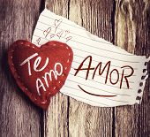 "image of miss you  - ""Te Amo Amor"" (In portuguese - I Love You, honey) written on a peace of paper and a heart on a wooden background - JPG"